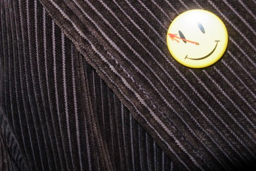 The pin button smile of the The Comedian is on the Kain Malcovich's jacket